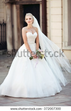 Beautiful fairytale blonde bride posing with bouquet in old italian street