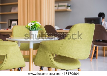 Beautiful fake flower in vase on white table in room