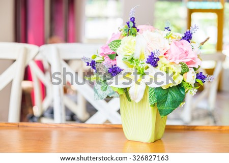 Beautiful fake plastic flower in vase decoration in living room