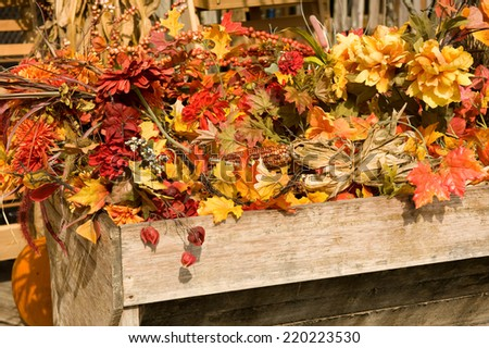 Beautiful fall centerpiece with flowers and leaves  - stock photo