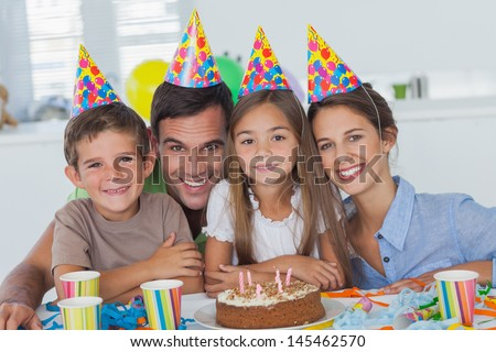 Beautiful family celebrating a party with a chocolate birthday cake - stock photo