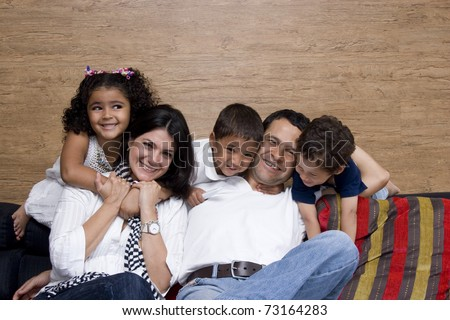 Beautiful family enjoying, mom and dad playing with their children at home