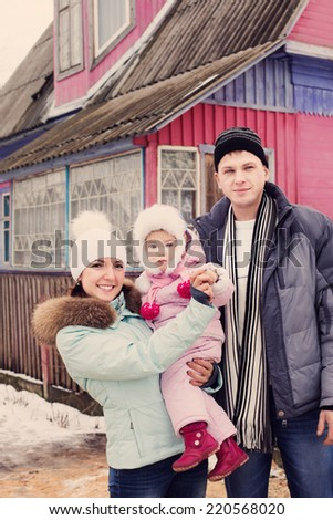 Beautiful family in warm clothes standing  of his house in winter