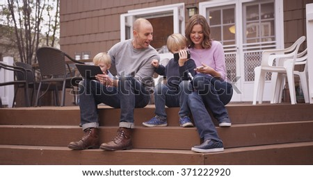 Beautiful family looking at handheld devices outside. - stock photo