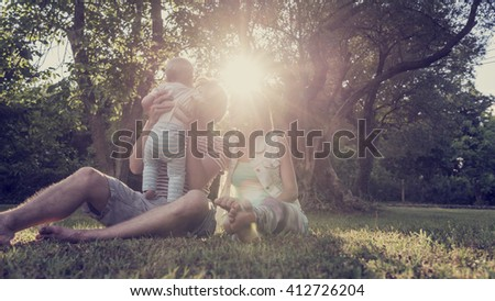 Beautiful family moment - young couple sitting in grass in a park with trees while father holds their toddler child lit by a bright sunlight. With retro filter effect. - stock photo