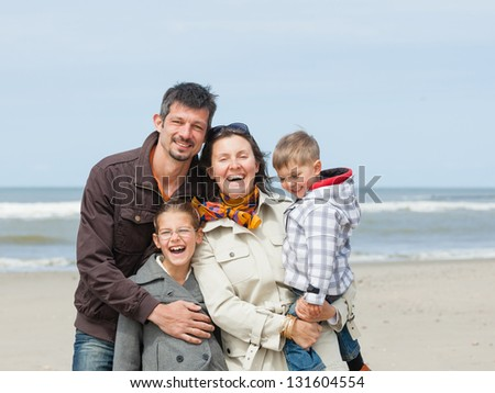 Beautiful family of four walking on the beach. Holland - stock photo