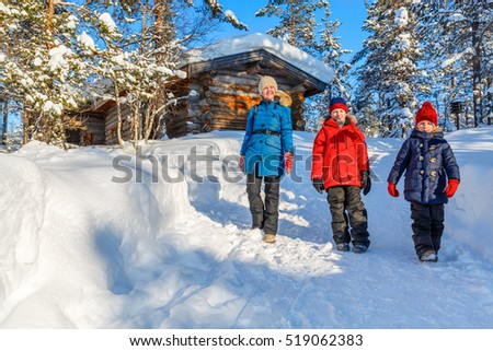 Beautiful family of mother and kids enjoying snowy winter day outdoors