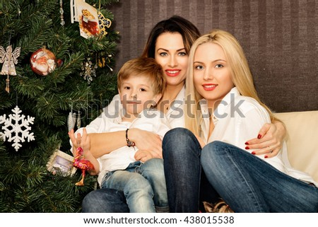 Beautiful family of mother, daughter and a son sitting on the sofa at the Christmas tree.