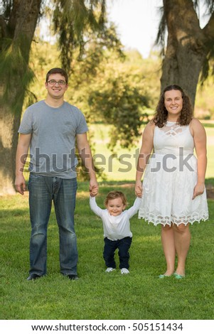 Beautiful family of three posing in a park. Family pictures. Family portraits