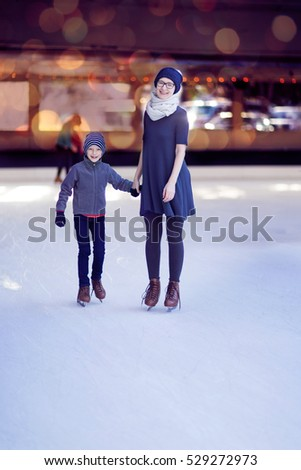 beautiful family of two enjoying winter holidays and ice skating at outdoor rink, winter vacation activity