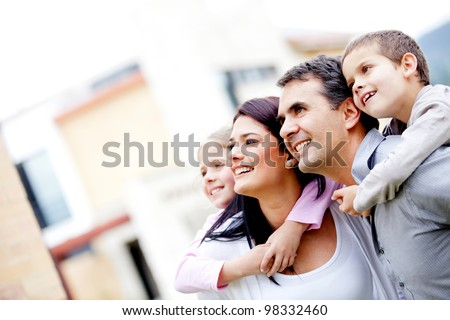 Beautiful family outside their house looking away - stock photo
