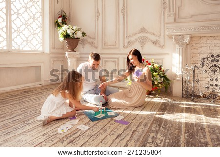 Beautiful family playing  board game on floor in luxury living room; family of tree sitting on floor and playing; father, mother and daughter playing together; happy family playing game on sunny day - stock photo
