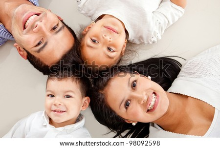 Beautiful family portrait laying down with heads together - stock photo
