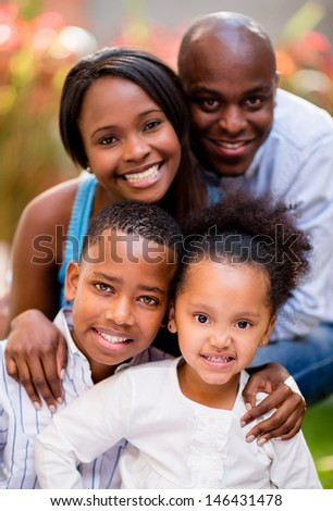 Beautiful family portrait looking very happy outdoors  - stock photo