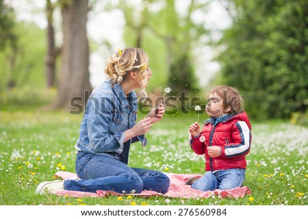Beautiful family portrait of young mother and her cute son blowing dandelions in nature - stock photo