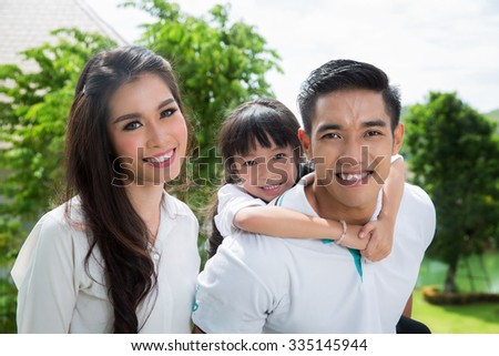 Beautiful family portrait smiling outside their new house - stock photo