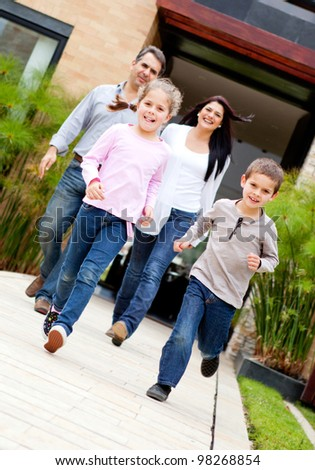 Beautiful family running in front of a house - stock photo