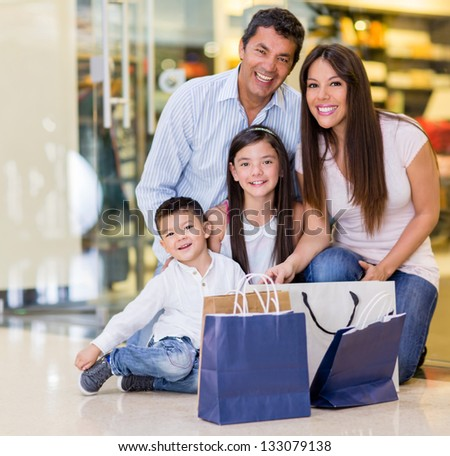 Beautiful family shopping at the mall and looking very happy - stock photo