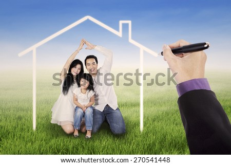 Beautiful family sitting on the meadow under a dream home, shot outdoors
