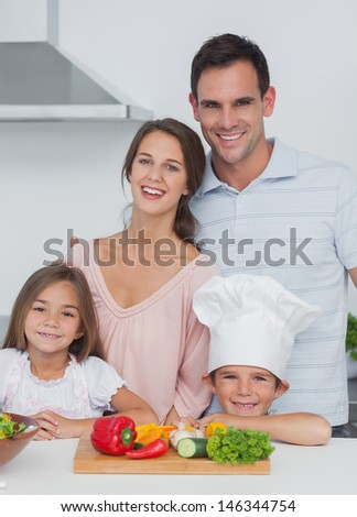 Beautiful family standing in the kitchen with a wooden board with vegetables on the table - stock photo