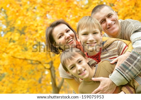 beautiful family together for a walk during the fall of the leaves in the park