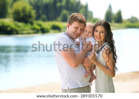 beautiful family with a baby in the park - stock photo