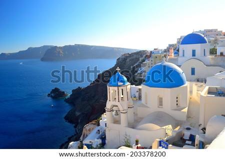 beautiful famous Santorini blue dome churches of Agios Spyridonas (St. Spiridon) and Anastasis (Resurrection) in Oia village - Santorini (Thira), Cyclades islands, Greece - stock photo
