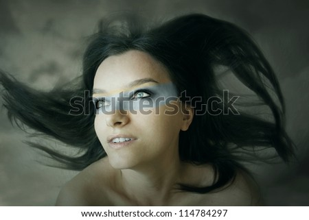 Beautiful fantasy expressive portrait of a girl with long hair in the wind and extravagant makeup in the cloudy sky background