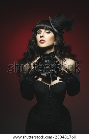 Beautiful fantasy gothic vampire brunette woman in sexy black satin corset, burlesque hat, jabot and long gloves - stock photo