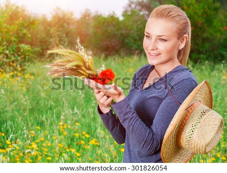 Beautiful farmer girl standing on green floral field in mild sunset light, holding in hands ripe spikelets of wheat and red poppy flowers bouquet, enjoying autumn harvest - stock photo