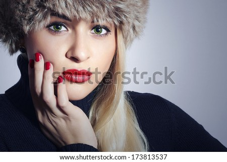 Beautiful Fashion Blond Woman in Fur. Beauty Girl with Green Eyes and Red Lips. Winter Style. Red Manicure.