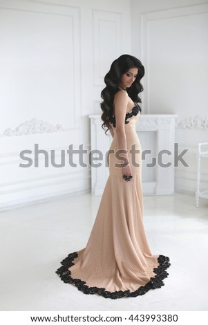Beautiful fashion brunette woman in elegant dress with long wavy hair style posing by wall in white modern interior, full length portrait. - stock photo