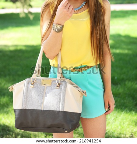 Beautiful fashion brunette young woman with big handbag posing outdoor in summer. fresh bright dress - stock photo