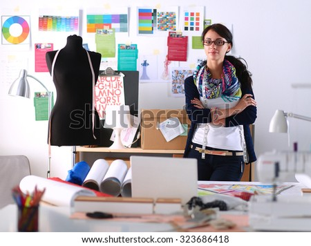 Beautiful fashion designer standing in studio - stock photo
