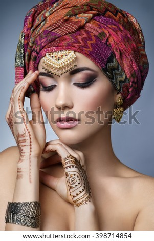 Beautiful fashion east  woman portrait with oriental accessories- earrings, bracelets and rings. Indian girl with  henna tattoos and beauty jewels. Hindu model with perfect make-up. India. Asia