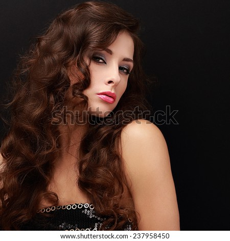 Beautiful fashion female model with long brown hair looking sexy on black background