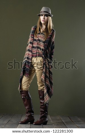 Beautiful fashion girl in hat standing posing on wooden floor