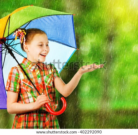 Beautiful fashion girl with a rainbow umbrella - stock photo