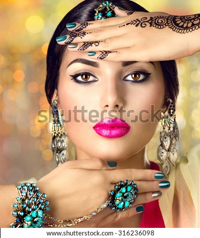 Beautiful fashion Indian woman portrait with oriental accessories- earrings, bracelets and rings. Indian girl with black henna tattoos and beauty jewels. Hindu model with perfect make-up. India - stock photo