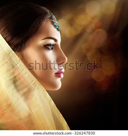 Beautiful fashion Indian woman profile portrait with oriental accessories. Indian girl with beauty jewels. Hindu model with perfect make-up. India - stock photo