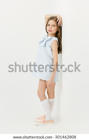 Beautiful fashion little girl in blue dress with bow standing near white wall - stock photo