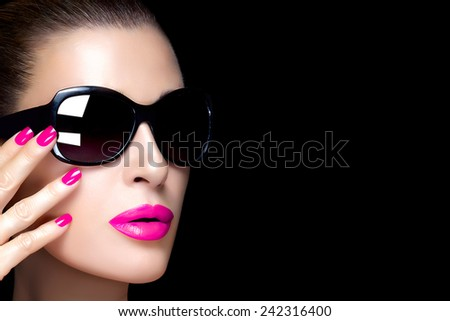 Beautiful fashion model face with oversized black sunglasses. Bright makeup and manicure. High fashion portrait isolated on black background with copy space for text. Beauty and fashion concept. - stock photo