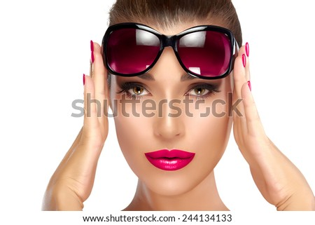 Beautiful fashion model girl holding her shades on forehead while looking at camera. Bright makeup and manicure. High fashion portrait isolated on white background. Beauty and fashion concept.