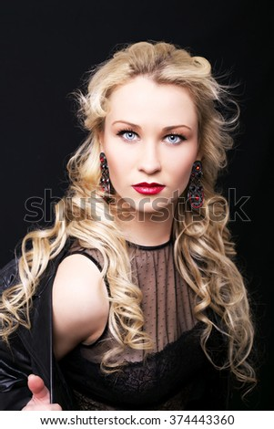 Beautiful fashion model girl with blond hair. Portrait of glamour woman with bright makeup isolated on black background.