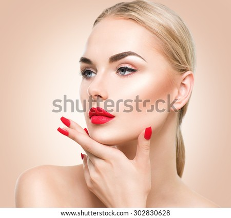 Beautiful fashion model girl with blond hair. Red lipstick and nails. Portrait of glamour woman with bright makeup over beige background. Beauty female face close up with perfect make up and manicure - stock photo