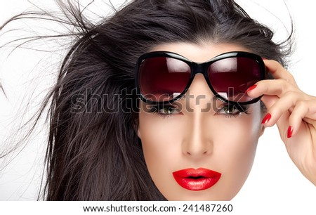Beautiful fashion model girl with healthy long hair in motion holding her shades on forehead while looking at camera. Isolated on white background. Beauty and fashion concept.