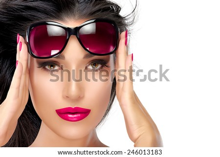 Beautiful fashion model girl with healthy long hair in motion holding her shades on forehead while looking at camera. Isolated on white background with copy space for text. Beauty and fashion concept.