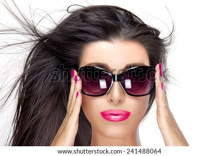 Beautiful fashion model girl with healthy long hair in motion in stylish oversized sunglasses. Bright makeup and manicure. High fashion portrait isolated on white. Beauty and fashion concept.