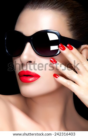 Beautiful fashion model girl with stylish oversized black sunglasses. Bright makeup and manicure. High fashion portrait isolated on black background. Beauty and fashion concept.