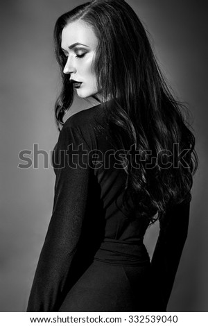 Beautiful Fashion model in black dress in studio,black and white photo